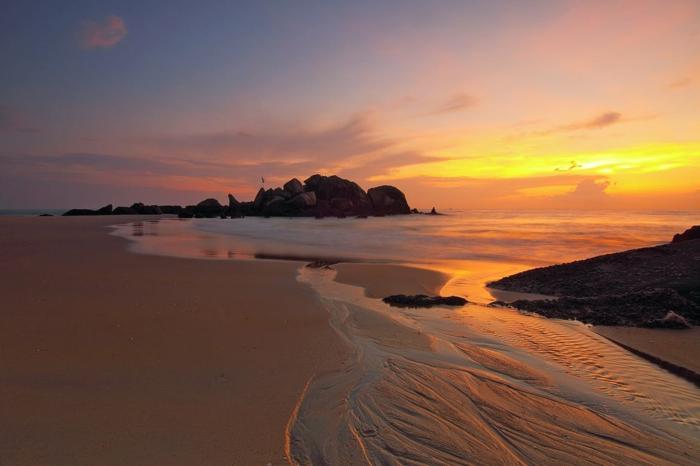 lieu paradisiaque, paysage paradisiaque, coucher de soleil au-dessus de la mer, ciel bleu avec des nuages en jaune et en orange, sable beige
