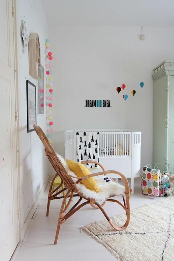 décoration chambre bébé fille, chaise en rotin tressé en couleur claire, tableau chambre bébé, lit bébé en forme ovale, tapis couleurs pastels