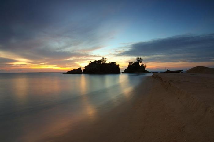 paysage de reve, iles paradisiaques, trois silhouettes de rochers a l'horizon, eaux tranquilles, quasi irréelles, jolie paysage