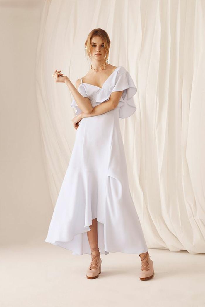 femme en robe blanche avec devant asymétrique et volant latéral, tenue de fête femme, une épaule nue, chaussures beiges bouts arrondis