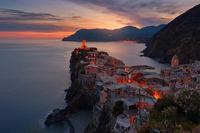 jolie paysage dans un village grec au coucher du soleil, village de pêcheurs, lumières rouges entre les maisons, rocher blanc qui surplombe la me , montagnes aux silhouettes noires