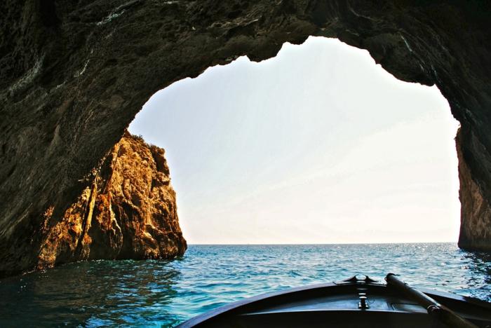 la sortie de la grotte avec une petite barque de pêcheurs, ciel sans nuages, eaux bleues Grotta azzurra, roches marrons et grises