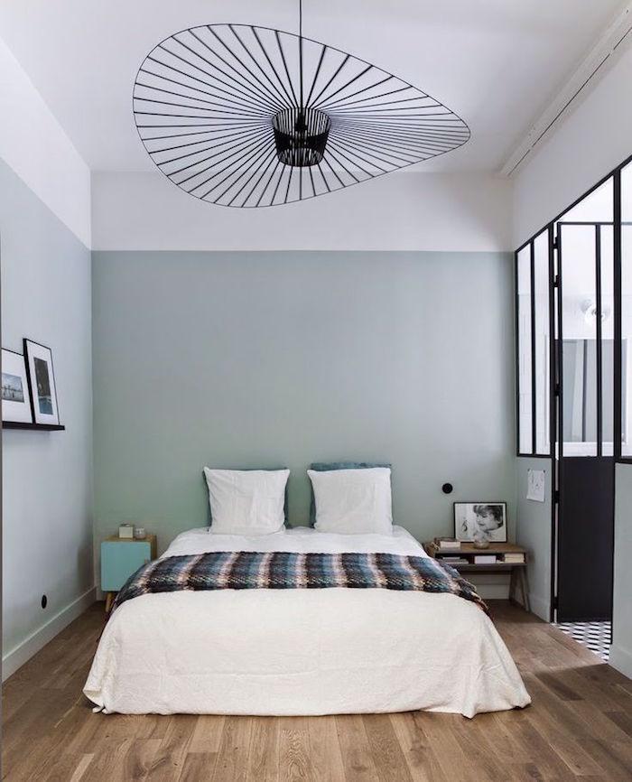 loft avec chambre adulte à la décoration simple et moderne, peinture murale gris vert, lustre design en metal