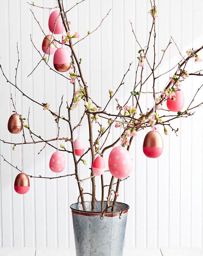 arbre de paques en branches fleuries avec des oeufs rose et or dans un seau, deco paques original pour votre interieur maison