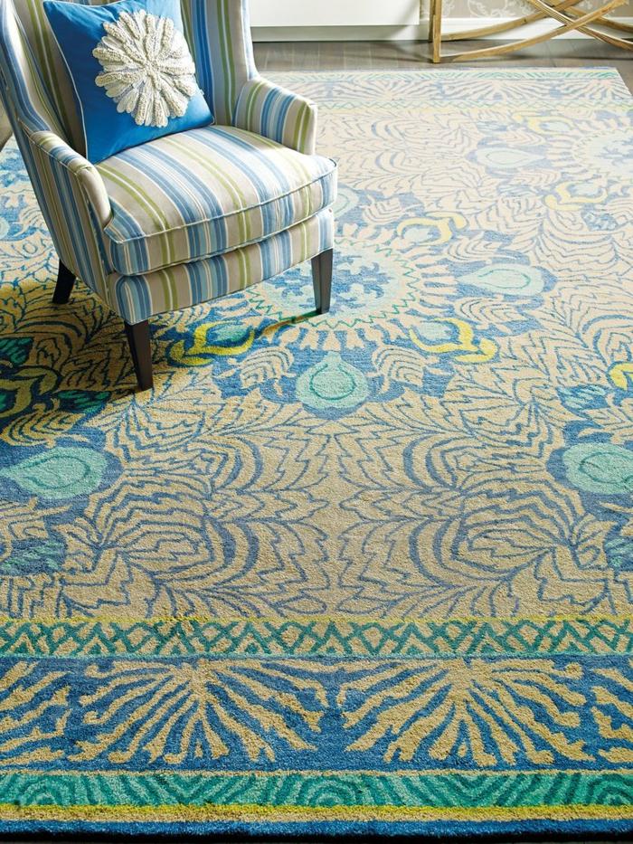 salon avec deco zen, tapis en nuances pastels et fauteuil aux motifs assortis, coussin en bleu roi avec motif blanc flocon de neige, table aux pieds en bois clair