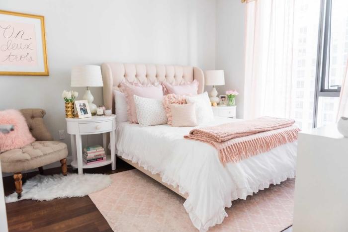 chambre à coucher blanche au parquet de bois foncé, grand tapis de couleur rose poudré et petit tapis à imitation peau animal blanc