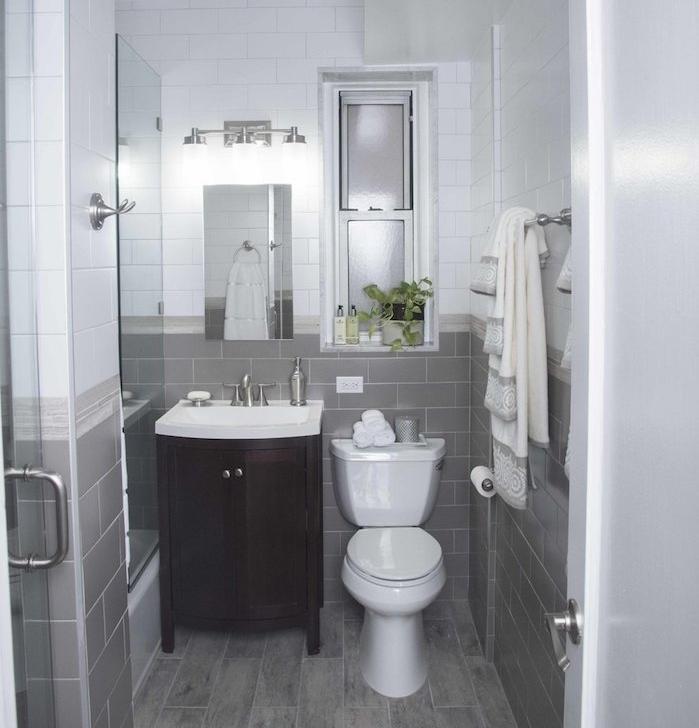 salle de bain petite surface blanche et grise, carrelage gris et blanc et sol avec parquet gris, petit miroir, meuble sous vasque bois marron