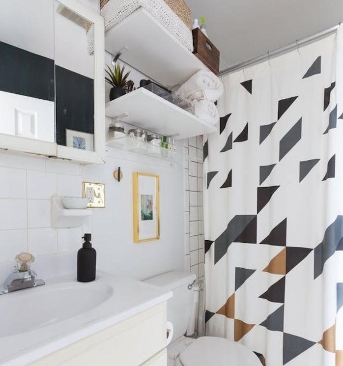 exemple petite salle de bain avec dea étagères au-dessus de toilette, rideau de douche à motifs géométriques, placard avec miroir intégré