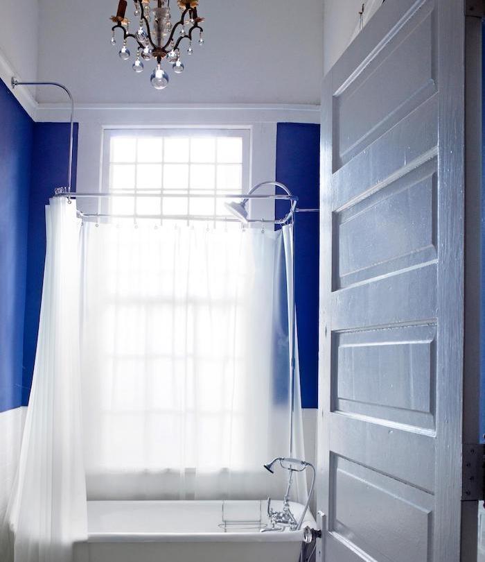 petite salle de bain design luxe, mur bleu marine, baignoire blanche et rideau de douche blanc, lustre luxe