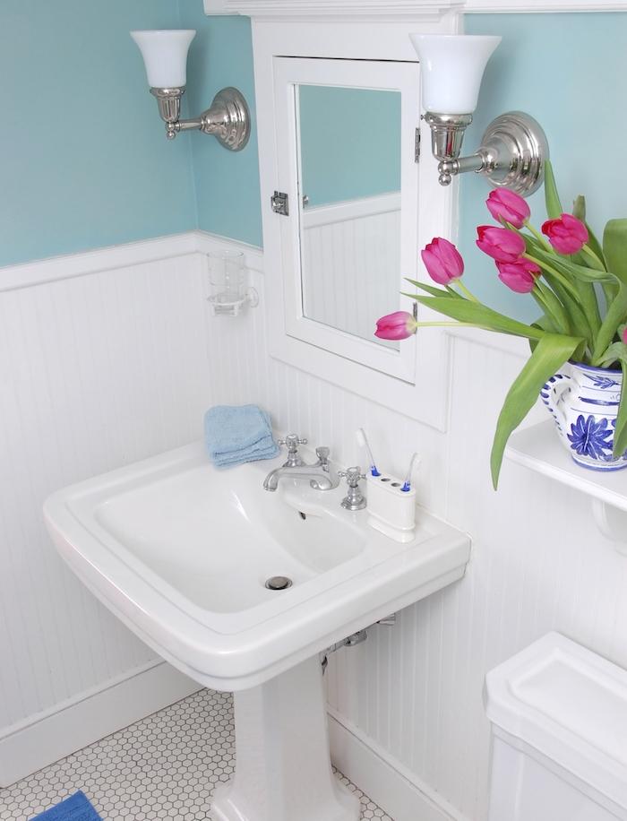 exemple de petite salle de bain design, lavabo console, miroir, peinture mur bleu, sol carrelage vintage, bouquet de tulipes