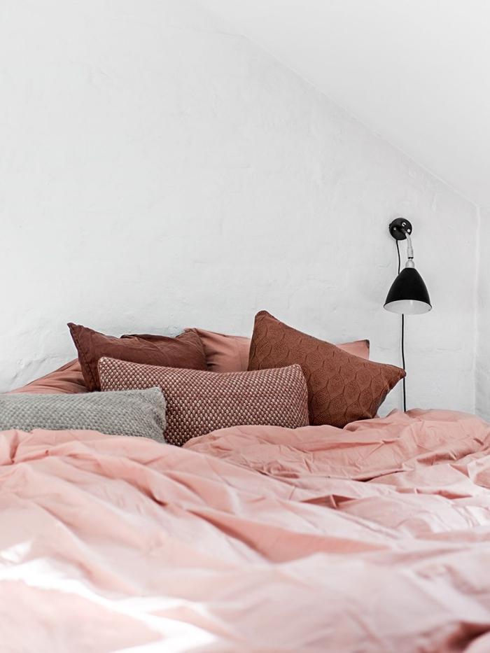 déco de chambre à coucher sous pente avec grand lit couvert de linge rose poudré et petits coussins décoratifs