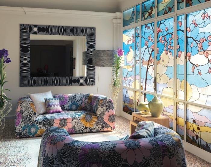 feng shui salon, deco epuree, deux canapés aux motifs fleuris en bleu et rose, grand miroir rectangulaire au cadre aux motifs ethniques en noir et blanc, panneaux coulissants en style vitrage avec paysage nature asiatique typique, cerisiers durant le printemps et la nature qui se réveille