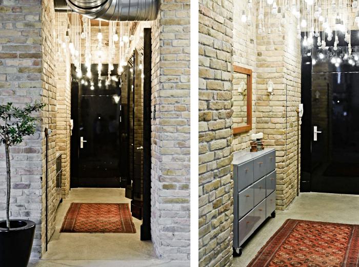 deco couloir aux murs en pierre et tuyaux apparents, éclairage moderne avec cordes et ampoules électrique à différentes longueurs