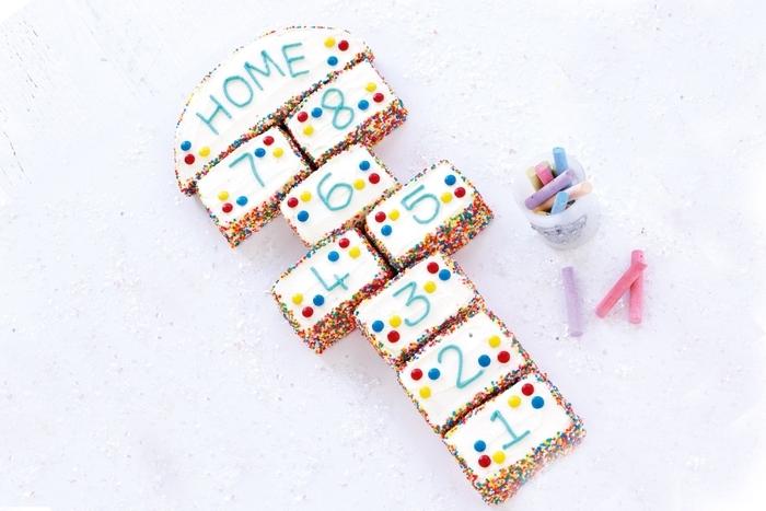 idée pour un gateau d anniversaire original en forme de marelle composé de gâteaux individuels numérotés au glaçage blanc