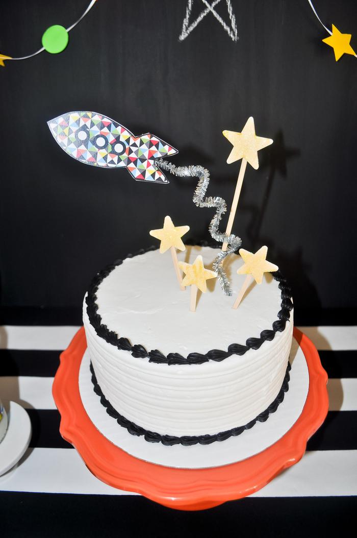 gateau anniversaire facile à préparer au glaçage blanc et noir sur les bords décoré avec des cake-toppers à thème espace