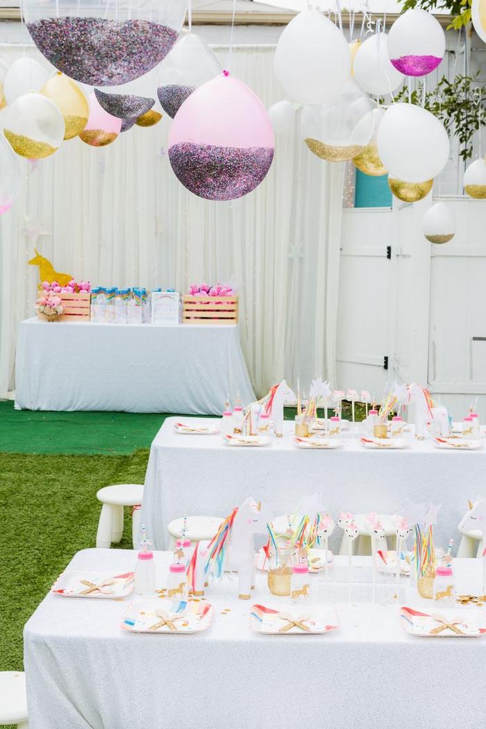 un anniversaire theme licorne en rose, blanc et doré avec une décoration en toute légèreté de ballons personnalisés avec des paillettes