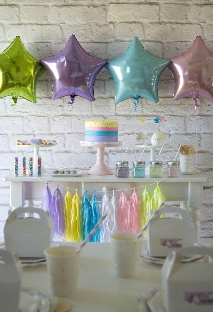 un candy bar en tons pastel décoré de ballons aluminium en forme d'étoiles, une guirlande de tassels et un gateau licorne au glaçage arc-en-ciel