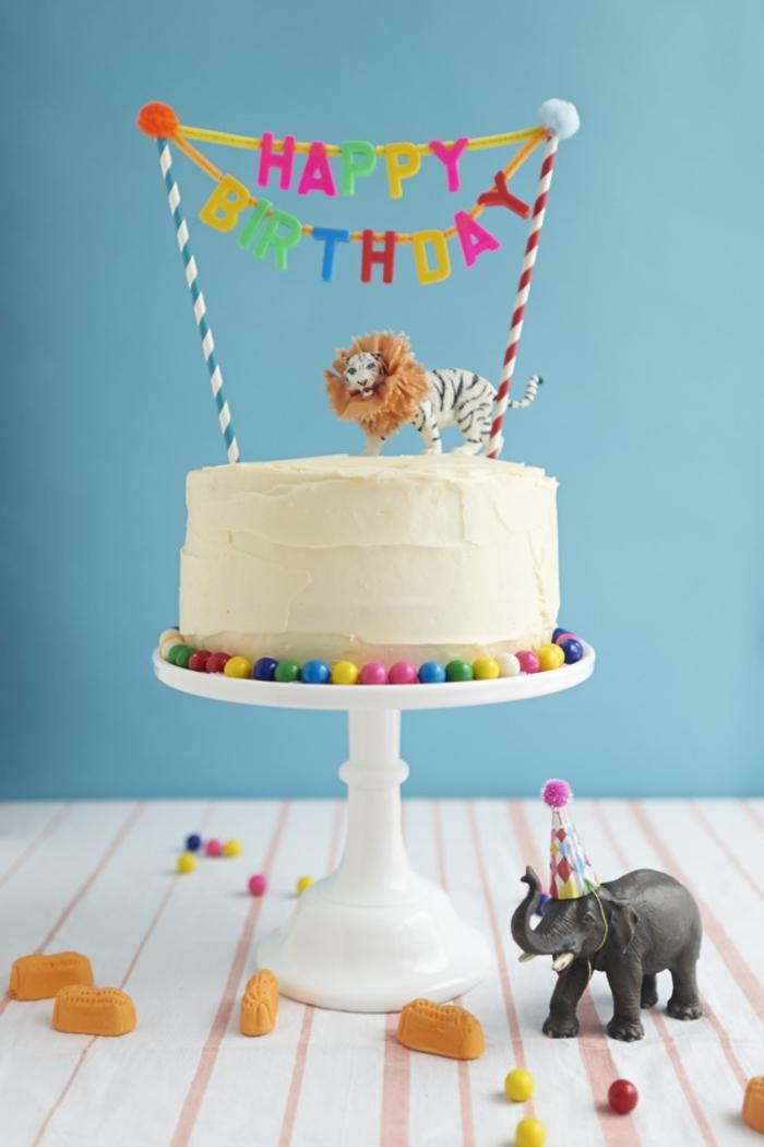idée pour une décoration de gateau anniversaire facile avec une bannière multicolore et des figurines d'animaux d'afrique
