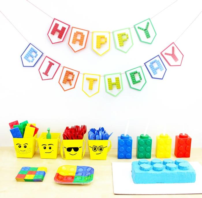 un gateau d'anniversaire personnalisé en forme de brique lego recouvert de nappage bleu et un buffet d'anniversaire à thème lego