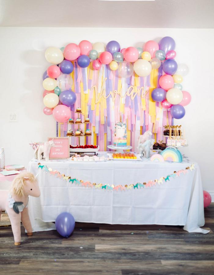 idée déco pour un anniversaire licorne avec un mur de serpentins avec des ballons pastel en bordure
