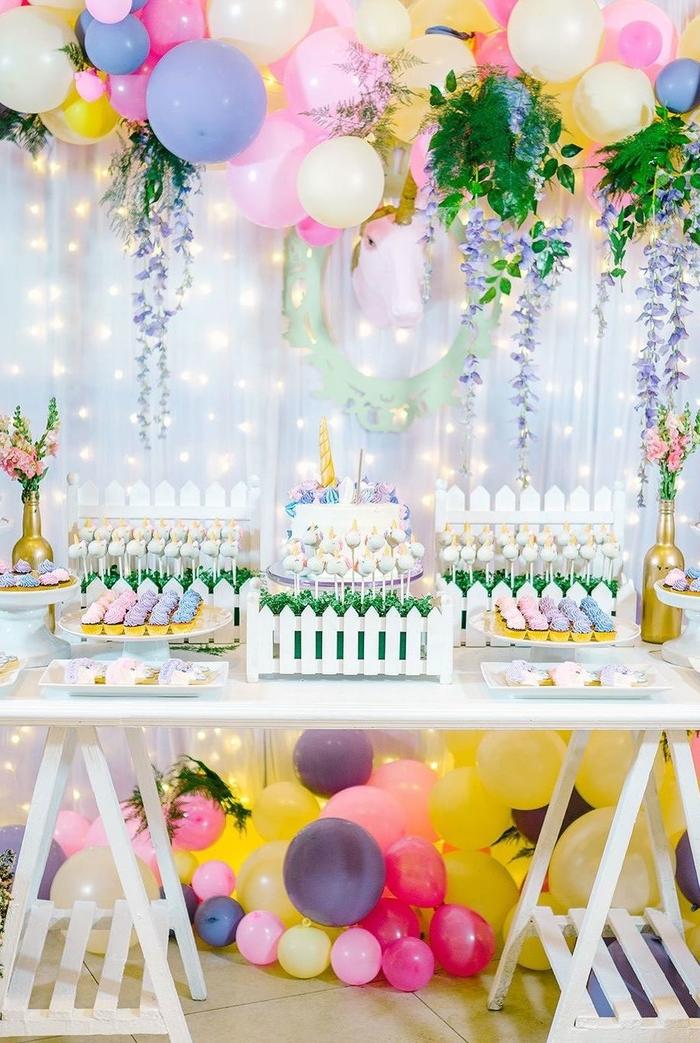 décoration de buffet d'anniversaire champêtre dans l'esprit garden party avec un arc en ballons, des guirlandes florales et un objet licorne trophée en carton
