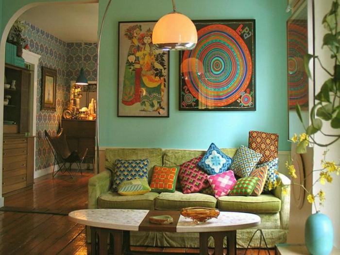 tabe blanche ovale, canapé vert, peintures encadrées, plafonnier pendant, plante suspendue, plancher en bois