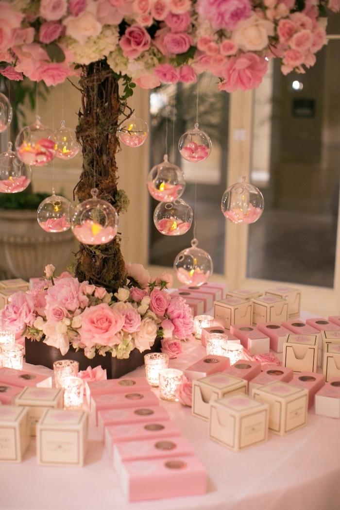 decoration mariage romantique en rose et blanche avec bougies et roses, produits cosmétiques pour les invités