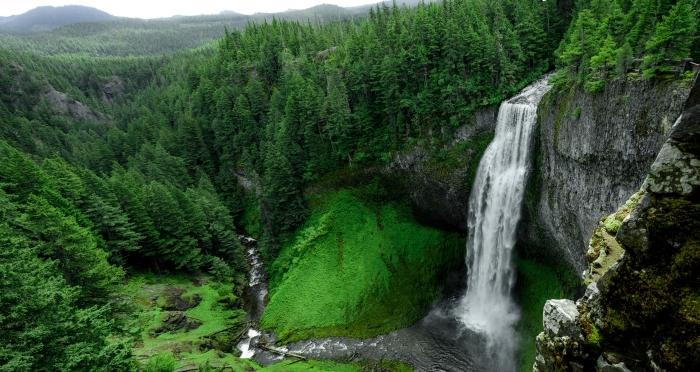 beau fond d écran avec chute d'eau et rivière dans une forêt verte d'arbres conifère et une vue vers les collines