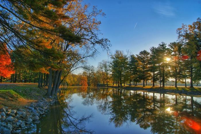 fond ecran paysage, foret en automne, avec des belles touches de rouge, paysage paradisiaque, eaux tranquilles d'un fleuve, avec des cailloux gris sur ses bords, ciel bleu sans nuages