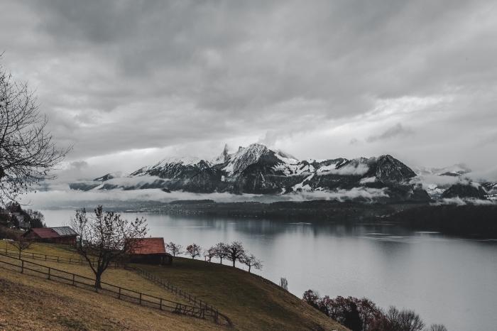 beau fond d écran avec paysage naturel, brouillard au-dessus des montagnes enneigées au bord d'un lac et champ vert