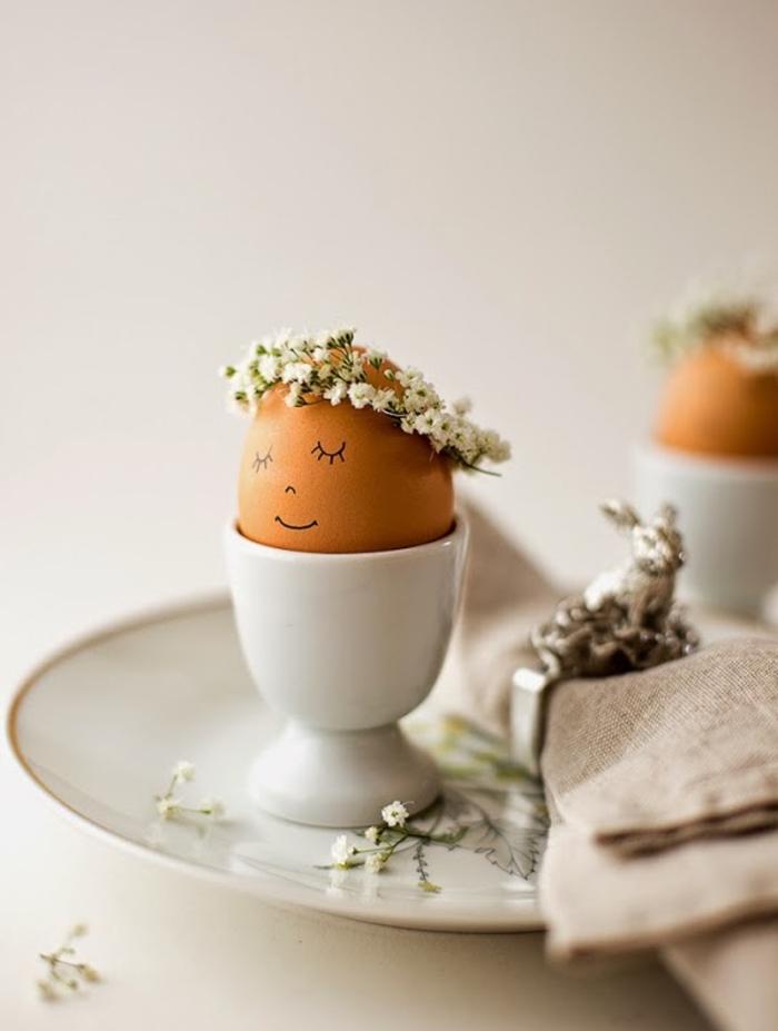 comment décorer une table de noel avec assiette blanche et coeurs à visage dessiné en marqueur noir et couronne de fleurs
