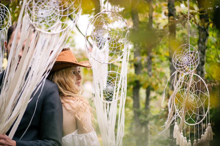 deco mariage boheme avec attrape reve geant blanc avec des chutes de ruban blanc et des pompons à franges blancs