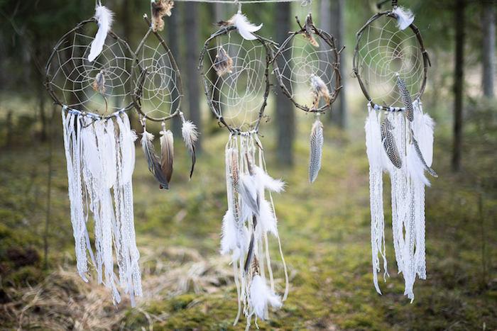 décoration extérieur forêt, attrape reve fabrication traditionnelle avec des cerceaux en branches naturelles, chutes de dentelle, plumes, filet blanc