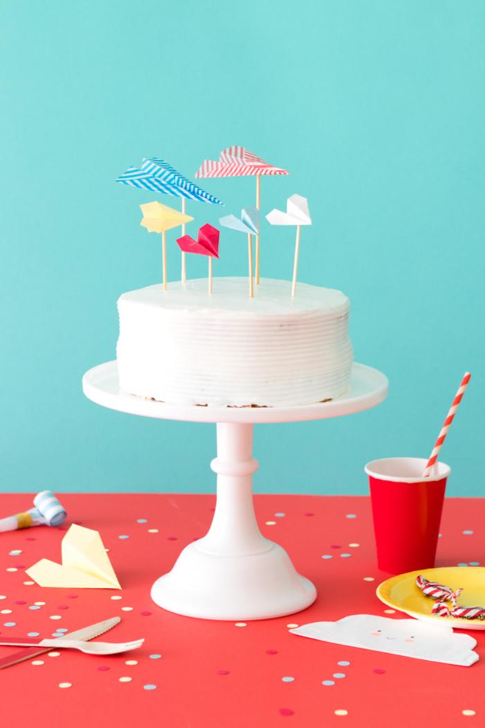 une décoration de gateau d'anniversaire au glaçage blanc avec des cake-toppers avions origami