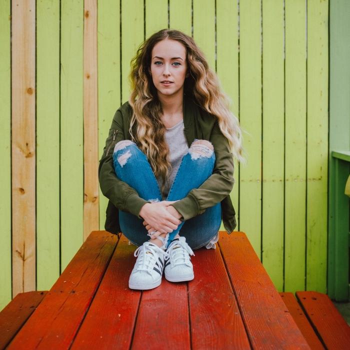 cheveux de couleur ombré longs et bouclés, tenue en veste kaki avec jeans déchirés, maquillage pour yeux bleus