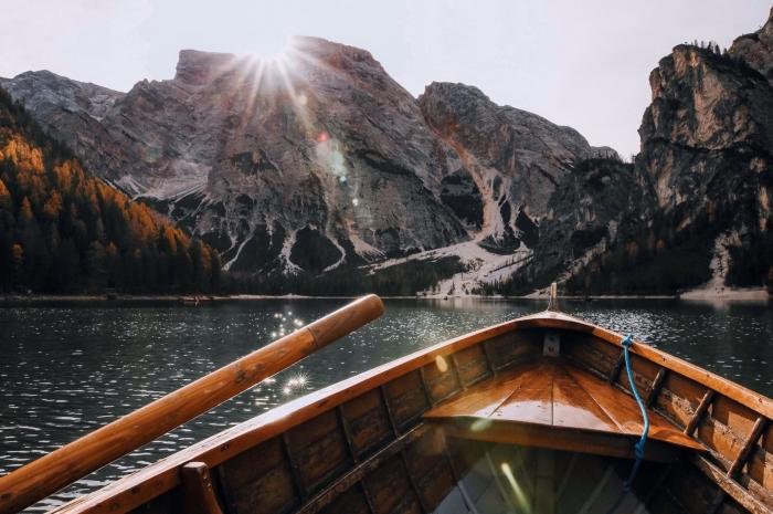 photo de bateau dans un lac au coeurs des montagnes, fond d écran jolie avec soleil au dessus des rochers