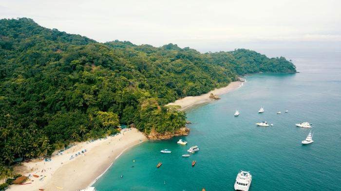 image fond d écran exotique, photo d'ile à végétation et sable doré avec eau turquoise et grands bateaux