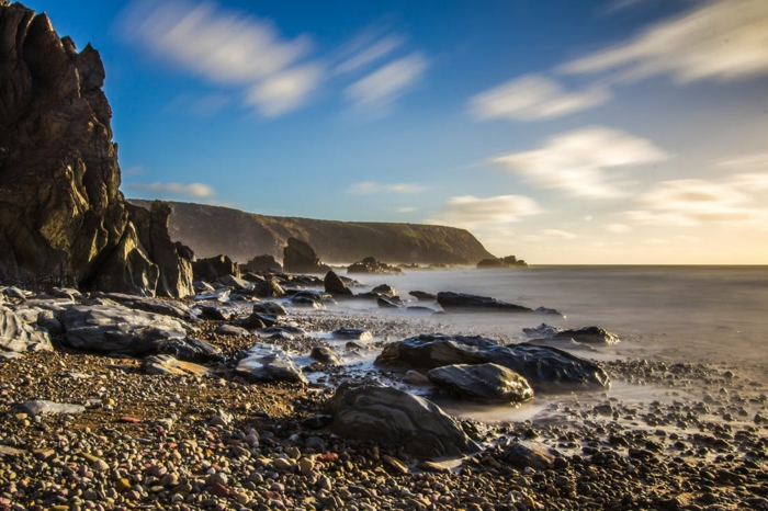 iles paradisiaques, paysage mer, paysage paradisiaque, ciel bleu avec des nuages blancs, rochers marrons horizon et grands cailloux au bord de la mer