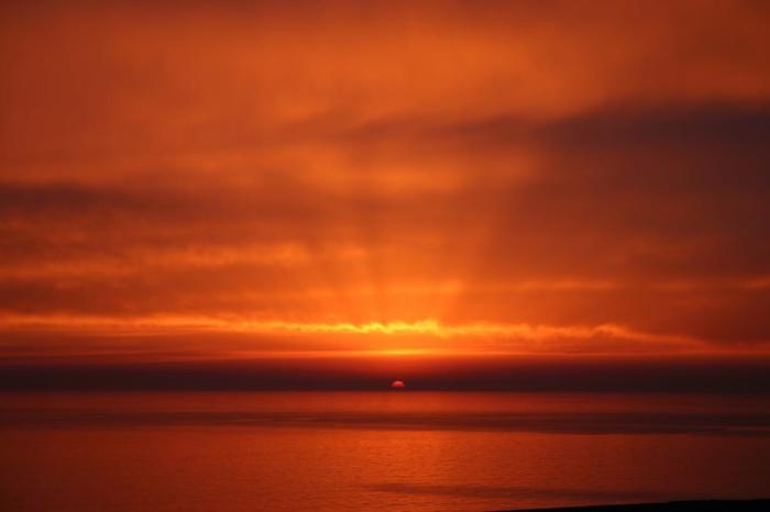 paysage en rouge, avec des rayons qui se filtrent a travers les nuages, mer tranquille, soleil couchant rouge, ambiance quasi irréelle, paix-et zen, dépaysement total, paysage paradisiaque