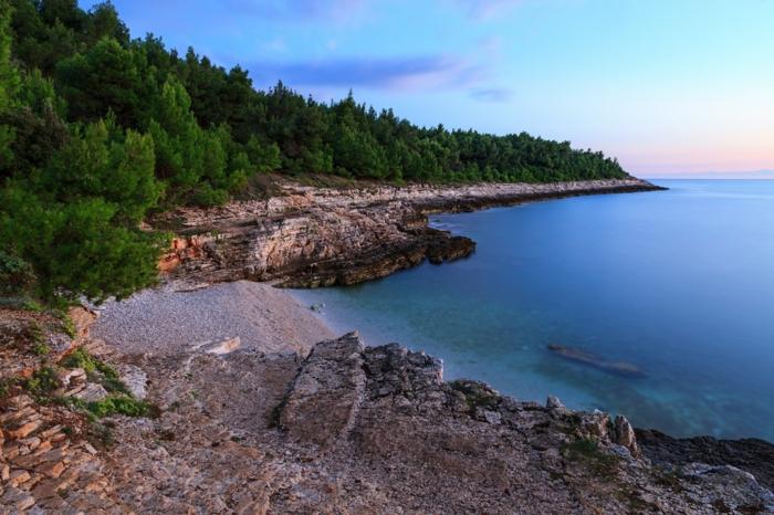 paysage lac, foret verte, rochers gris, ciel bleu nuances pastels, horizon tranquille, paysage désert, ambiance cool