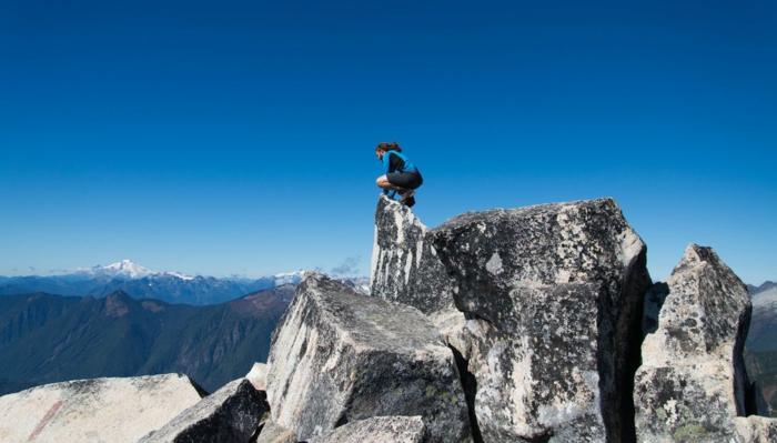 beau paysage, fond ecran paysage, homme sportif au sommet d'une roche en blanc et noir, ciel bleu sans nuages, vue magnifique d'en haut du rocher