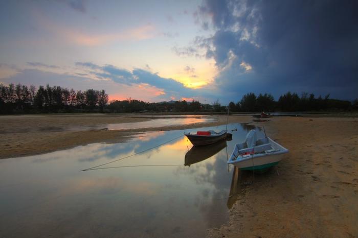 endroit paradisiaque, ciel aux mille nuances du rose et du pourpre, ambiance de rêve, canal étroit qui s'unie a la mer, deux barques au coucher du soleil