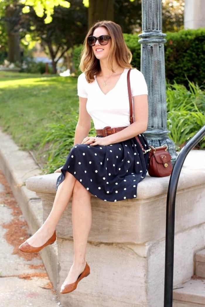 jupe légère en bleu marine aux pois blancs, T-shirt blanc, chaussures plates pointues en couleur tabac, petit sac en marron, tenue chic, femme bien habillée