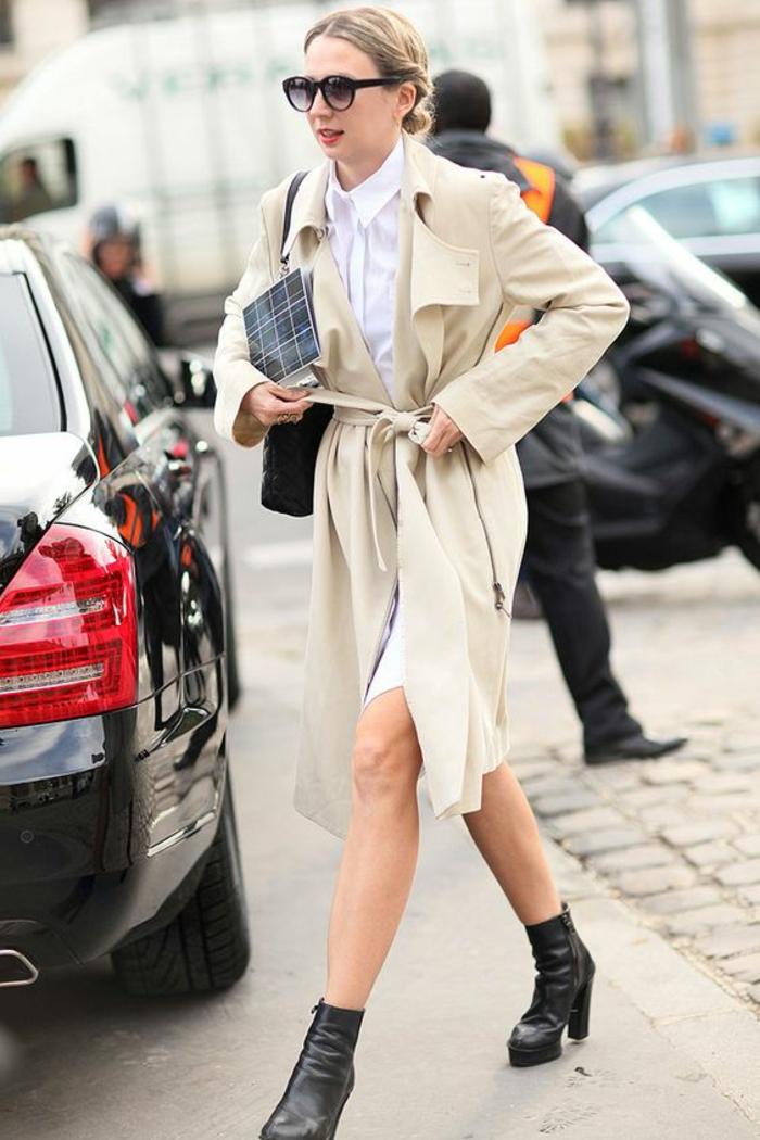tenue décontractée chic femme, imperméable en couleur crème, bottines noires, chemise blanche manches longues, look de femme active