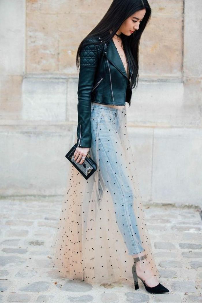 jeune femme en jupe de tulle a pois noirs couleur ivoire transparent, portée sur un jean en denim bleu clair, mini sac pochette noir, veste en cuir noir, chaussures noires pointues, tenue casual