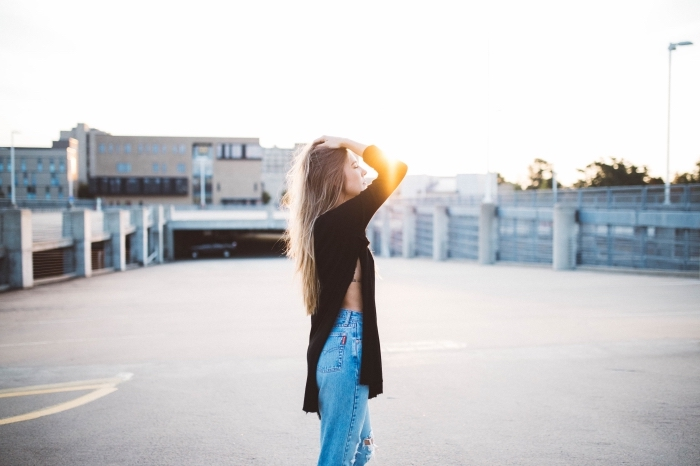 ombré hair brune sur cheveux longs raids, tenue chic en jeans taille haute combinés avec tunique noire à design asymétrique