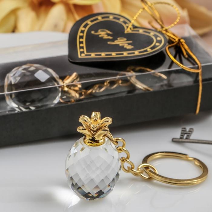 idée cadeau mariage pas cher, modèle de porte-clé à design ananas en ver et finition doré posée dans une boîte élégante noire
