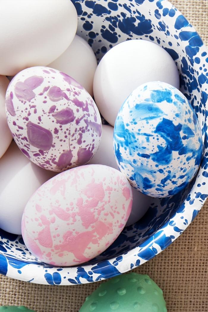 bol à design marbre blanc et bleu foncé avec oeufs à coquille blanche décorés en peinture alimentaire design marbre coloré