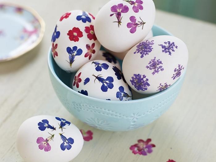 idée pour decoration paques facile sur coquilles blanches avec stickers autocollants à design floral en violet bleu et rouge