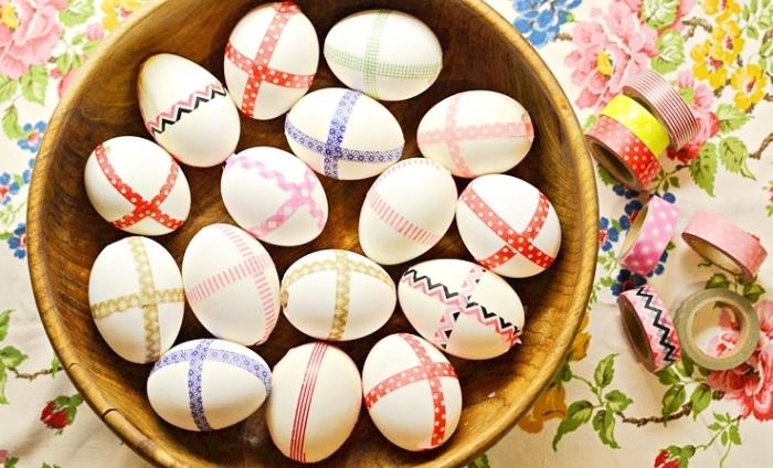 exemple de décoration de paques facile avec ruban adhésif à design coloré et motifs géométriques dans un bol de bois